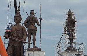 Thai workers put the final touches on statues of Thai…