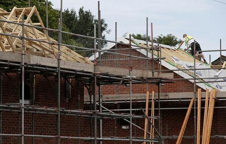 A man works on the roof of a building site in Cheadle Hume