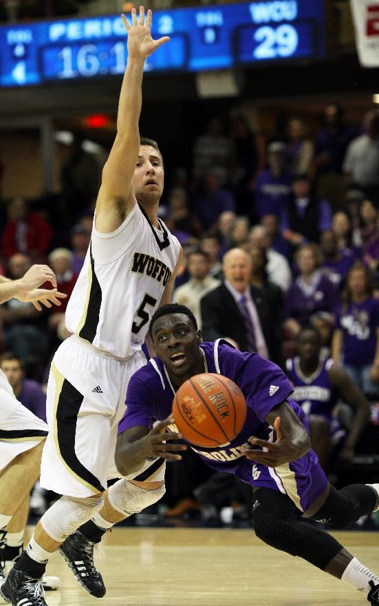 Wofford's Eric Garcia (left) guards Western Carolina's James Sinclair (right) as he dives for the ball during the second half of the NCAA college basketball championship game of the Southern Conference tournament in Asheville, N.C., Monday, March 10, 2014. (AP Photo/Adam Jennings)