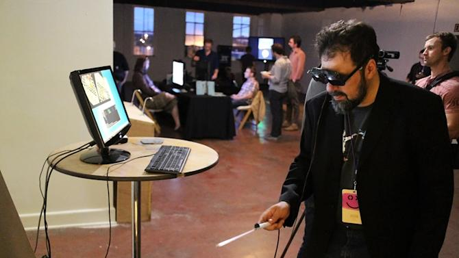 This Sept. 20, 2013 image released by Technical Illusions shows TextFiles.com founder and owner Jason Scott using the CastAR augmented reality 3D glasses in Portland, Ore. Wearable technology such as CastAR was among the topics discussed at the Game Developers Conference Next at the Los Angeles Convention Center on Nov. 5-7, 2013. (AP Photo/Technical Illusions/Jenesee Grey)