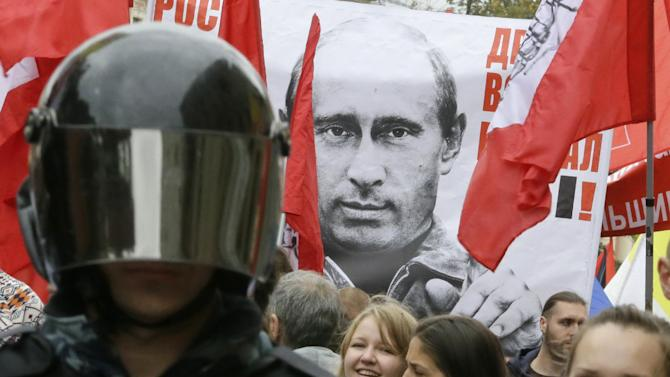 """Protesters hold a poster depicting Russia's President Vladimir Putin as they march during a protest rally in St. Petersburg, Russia, Saturday, Sept. 15, 2012. The sign reads: """"Prices, tariffs and poverty rise, you chose all this"""".  Thousands of protesters marched across downtown Moscow  and St. Petersburg on Saturday in the first major rally in three months against President Vladimir Putin, while defying the Kremlin's ongoing efforts to crackdown on opposition. (AP Photo/Dmitry Lovetsky)"""