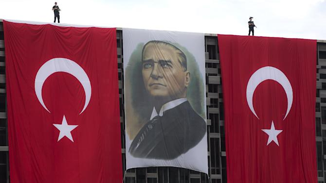 Riot policemen stand on a building overlooking Taksim square, decorated with Turkish flags and a portrait of Mustafa Kemal Ataturk, the founder of modern Turkey, in Istanbul, Turkey, Wednesday, June 12, 2013. Riot police fired tear gas, water cannon and rubber bullets in day-long clashes that lasted into the early hours Wednesday, battling protesters who have been occupying Istanbul's central Taksim Square and its adjacent Gezi Park in the country's most severe anti-government protests in decades.(AP Photo/Vadim Ghirda)