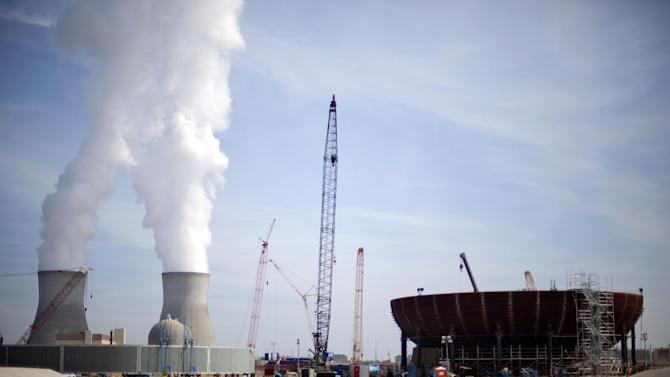 FILE - In this Feb. 15, 2012 file photo, cooling towers for units 1 and 2 are seen at left as the new reactor vessel bottom head for unit 3 stands under construction at right at the Vogtle nuclear power plant in Waynesboro, Ga.   Vogtle initially estimated to cost $14 billion, has run into over $800 million in extra charges related to licensing delays. A state monitor has said bluntly that co-owner, Southern Co. can't stick to its budget. The plant, whose first reactor was supposed to be operational by April 2016, is now delayed seven months.(AP Photo/David Goldman, File)