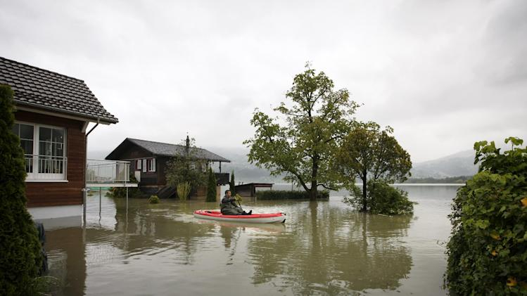 Daniel Dettling leaves his home in a boat at lake Lauerzersee, in Lauerz, Switzerland, Sunday, June 2, 2013. Heavy rainfalls cause flooding along rivers and lakes in Germany, Austria, Switzerland and the Czech Republic. (AP Photo/Keystone, Alexandra Wey)