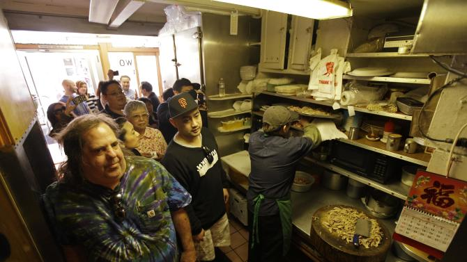 "Sam Begler, left, and other customers wait in the kitchen for a table at the Sam Wo restaurant in Chinatown in San Francisco, Friday, April 20, 2012. The 100-year-old Chinese restaurant known for having ""the world's rudest waiter"" is shutting its doors and serving its last customers Friday. (AP Photo/Eric Risberg)"