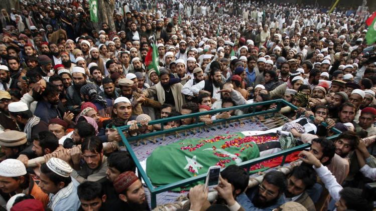 Supporters of Ahl-i-Sunnat Wal Jamaat (ASWJ), a political and religious group, carry the body of their party leader Maulana Shamsur Rehman, wrapped in the party's flag, while shouting slogans during a funeral procession in Lahore