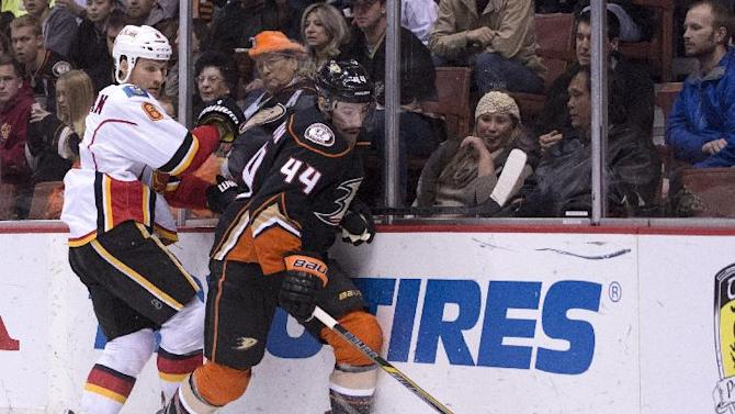 Anaheim Ducks Nate Thompson, right, controls the puck past the Calagry Flames Dennis Wideman during an NHL hockey game Tuesday, Nov. 25, 2014, in Anaheim, Calif. (AP Photo/The Orange County Register, Kyusung Gong)   MAGS OUT; LOS ANGELES TIMES OUT