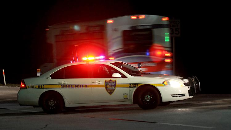 Police block the road to the Jacksonville International Airport terminal as a shuttle used to move people out of the airport drives by Tuesday, Oct. 1, 2013, in Jacksonville, Fla. The airport was evacuated after authorities found two suspicious packages. (AP Photo/The Florida Times-Union, Bruce Lipsky)