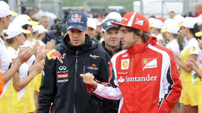 Red Bull driver Sebastian Vettel of Germany, left, and Ferrari driver Fernando Alonso of Spain, right, walk together to the drivers' parade before the Hungarian Formula One Grand Prix at the Hungaroring circuit outside Budapest, Hungary, Sunday, July 31, 2011. (AP Photo/Balazs Czagany)