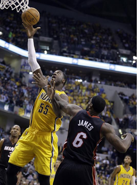 Indiana Pacers center Roy Hibbert (55) gets a bucket over Miami Heat forward LeBron James in the second half of an NBA basketball game in Indianapolis, Tuesday, Dec. 10, 2013