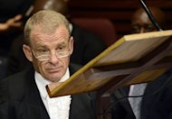 South African prosecutor Gerrie Nel attends the bail hearing of South African Olympic sprinter Oscar Pistorius at the Magistrate Court in Pretoria on February 19, 2013. Nel told the court Pistorius had armed himself, put on his prosthetic legs, walked seven metres and fired four shots into the bathroom door, hitting his terrified girlfriend three times and fatally wounding her