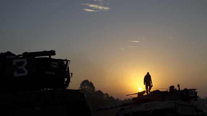 An Israeli soldier stands on top of a military vehicle as the sun rises in a staging area near the Israel Gaza Border, southern Israel, Tuesday, Nov. 20, 2012. Israeli aircraft on Tuesday battered the headquarters of the bank Gaza's Hamas leaders set up to sidestep international sanctions on their rule, as fitful efforts to negotiate an end to a week-old convulsion of violence moved to the highest reaches of diplomacy. The strike on the Islamic National Bank was part of a widening Israeli assault against Gaza militants, meant to quell rocket fire that has abruptly struck deep into Israel's heartland. U.N. chief Ban Ki-moon will be in Egypt and Israel on Tuesday to try his hand at prodding the two sides to reach a deal. (AP Photo/Ariel Schalit)