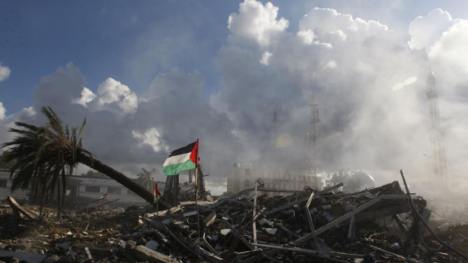 Smoke rises from the Hamas government building known as Abu Khadra that was destroyed in an Israeli air strike two days ago in Gaza City, Friday, Nov. 23, 2012. In Israel, a poll showed that about half of Israelis think their government should have continued its military offensive against Hamas. (AP Photo/Hatem Moussa)