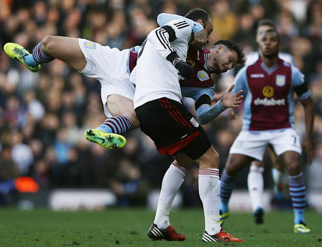 Fulham's Dimitar Berbatov is challenged by Aston Villa's Chris Herd during their English Premier League soccer match at Craven Cottage in London