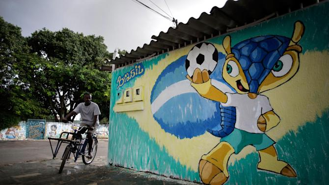 """A mural of the World Cup mascot """"Fuleco"""" covers a wall ahead of the World Cup in Brasilia, Brazil, Friday, May 23, 2014. Brasilia is one of the host cities for the upcoming international soccer tournament that starts in June. (AP Photo/Eraldo Peres)"""