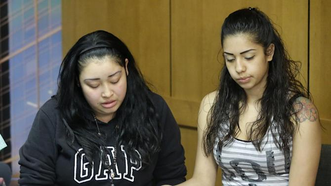 Johana Portillo, left, and her sister Ana Portillo, daughters of Riccardo Portillo hold hands during a news conference Thursday, May 2, 2013, at Intermountain Medical Center, in Murray, Utah. Ricardo Portillo, a Utah soccer referee, is in a coma after being punched by a teenage player unhappy with one of his calls _ and his family says their only hope is for a miracle. (AP Photo/Rick Bowmer)