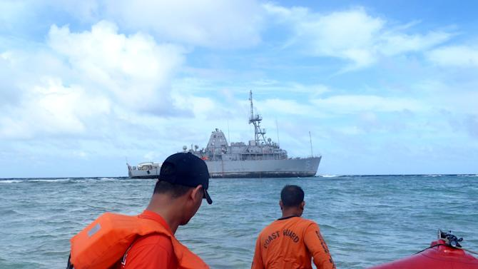 In this Jan. 22, 2013 photo released by the Philippine Coast Guard, coast guard divers approach the USS Guardian, a US Navy minesweeper, to assess the situation after it ran aground last week off Tubbataha Reef, a World Heritage Site in the Sulu Sea, 640 kilometers (400 miles) southwest of Manila, Philippines. A US. Navy official said the USS Guardian has been punctured and taking in water and has to be lifted off the rocks. (AP Photo/Philippine Coast Guard) EDITORIAL USE ONLY, NO SALES