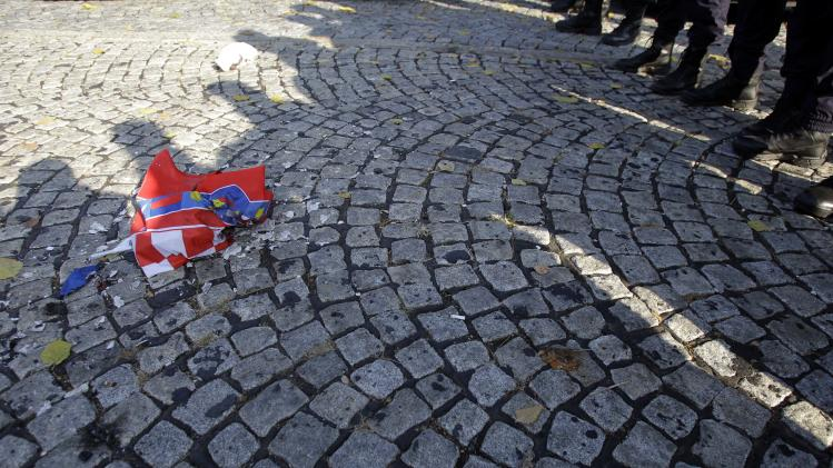 A burned Croatian flag seen in front of a police cordon during the protest in front of the presidency building in Belgrade, Serbia, Saturday, Nov. 17, 2012. A few hundred hardline Serbian nationalists  burned a Croatian flag angry that a U.N. war crimes court has overturned the convictions of two Croatian generals for murdering and expelling Serbs in a 1995 offensive. Serbia is furious that the appeals judges at the Hague court on Friday freed generals Ante Gotovina and Mladen Markac, who previously had been sentenced to lengthy prison terms for crimes against Serbs. (AP Photo/Darko Vojinovic)