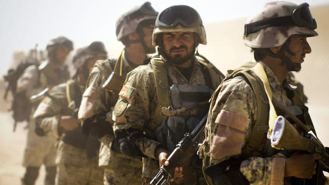 In this Friday, Oct. 19, 2012 photo, a member of Afghanistan's elite Civil Order Police squints from the dust as he and others line up before a patrol in Marjah, southern Helmand province, Afghanistan. As the U.S. and NATO close out their mission in Afghanistan preparing for the final withdrawal of combat troops by the end of 2014, the worry looms large that fresh outbursts of ethnically motivated fighting would send the country into a spiral of chaos and violence. (AP Photo/Anja Niedringhaus)
