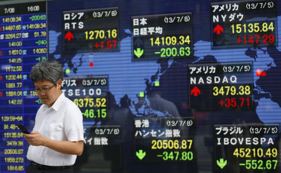 A man a mobile phone in front of an electronic stock indicator in Tokyo, Monday, July 8, 2013. Concern over China's slowdown weighed on Asian stock markets Monday after the head of the International Monetary Fund warned of a loss of momentum in emerging economies. (AP Photo/Shizuo Kambayashi)