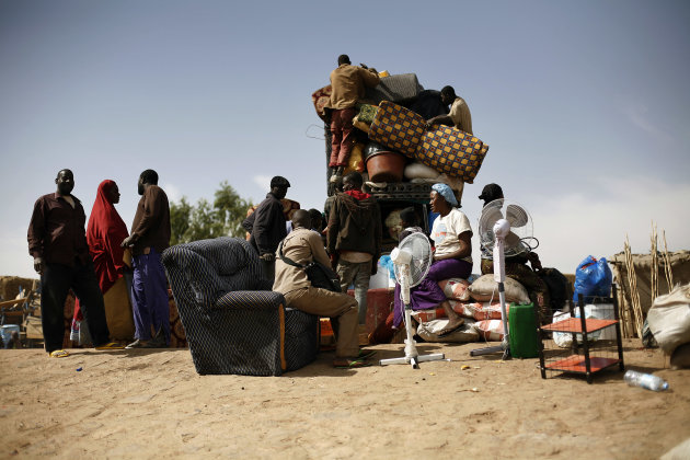 Malians fload a pickup truck with goods and furniture as they arrive after crossing the Niger river at Korioume Port, south of Timbuktu, Mali, Sunday Feb. 3, 2013. French troops launched airstrikes on Islamic militant training camps and arms depots around Kidal and Tessalit in Mali's far north, defense officials said Sunday, as the first supply convoy of food, fuel and parts to eastern Mali headed across the country. (AP Photo/Jerome Delay)