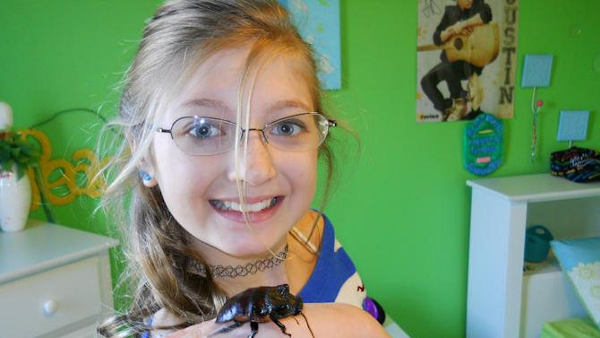 This undated photo provided by Orin McMonigle shows Gwynevere McMonigle with Dr. Phil, her pet hissing cockroach, Gromphadorhina portentosa. The most common pet roach, the hissing cockroach, is two to three inches long, and its name comes from the sound the insects make when disturbed, although they may lose the habit when they get used to being handled. Hissers make a good display not only due to their size, but also because they don't instinctively hide where they can't be seen. (AP Photo/Orin McMonigle)