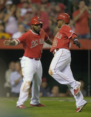 Los Angeles Angels' Erick Aybar, right, is congratulated by teammate Howie Kendrick after they both scored on a single by Gordon Beckham during the second inning of a baseball game against the Oakland Athletics, Thursday, Aug. 28, 2014, in Anaheim, Calif. (AP Photo/Mark J. Terrill)
