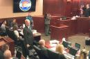 In this image taken from video, Judge Carlos A. Samour Jr., far right, swears in witness Caren Teves, whose son Alex was killed by James Holmes, who sits at far left in a gray shirt, before Teves testifies in the penalty phase of Holmes' trial in Centennial, Colo., Wednesday, Aug. 5, 2015. Caren Teves testified about the memories of her son Alex, who was 24 when he was gunned down in the Colorado movie theater. (Colorado Judicial Department via AP, Pool)