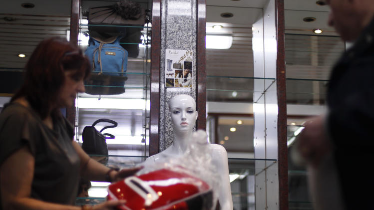Fernando Cruz, right, and Sandra Alves dismantle their clothes and accessories store after closing it down due to the lack of customers, in Lisbon, Monday, March 11, 2013. The couple, who owns two shops, closed one of them after weren't able to pay the rent and the suppliers. Portugal's statistics agency says the bailed-out country's economy contracted 3.2 percent last year, its sharpest downturn since 1975. (AP Photo/Francisco Seco)