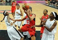 United States' guard Diana Taurasi, center, vies for the ball with Angola's forward Sonia Guadalupe, right, and Angola's center Luisa Tomas, left,  during their women's preliminary round group A basketball match at the 2012 Summer Olympics on Monday, July 30, 2012, in London. (AP Photo/Mark Ralston, Pool)