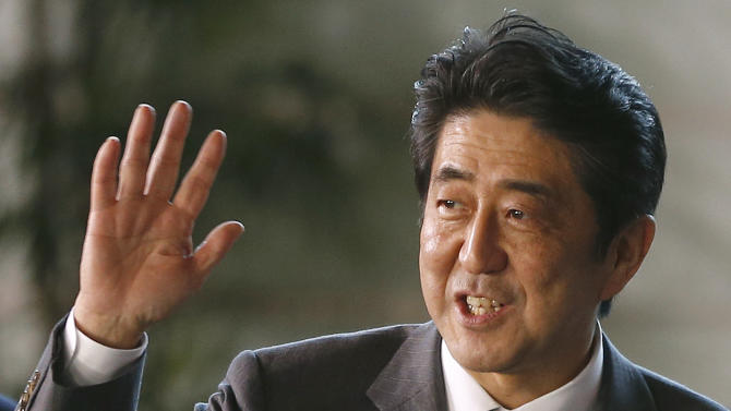 Japan's newly-named Prime Minsiter Shinzo Abe smiles as he waves at the media upon his arrival at the prime minister's official residence following his election at Parliament in Tokyo Wednesday, Dec. 26, 2012. Abe, whose nationalist positions have in the past angered Japan's neighbors, is the country's seventh prime minister in just over six years. (AP Photo/Shizuo Kambayashi)