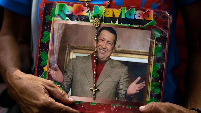 "A supporter of Venezuela's President Hugo Chavez holds a picture of him decorated with a rosary and the words in Spanish ""Merry Christmas"" outside the National Assembly in Caracas, Venezuela, Saturday, Jan. 5, 2013. Venezuelan lawmakers are meeting Saturday to select a new president of the National Assembly in a session that could give clues to the future of the country amid uncertainty about ailing Chavez. Just five days remain until Chavez's scheduled inauguration on Thursday and officials are suggesting the swearing-in could be delayed. (AP Photo/Fernando Llano)"