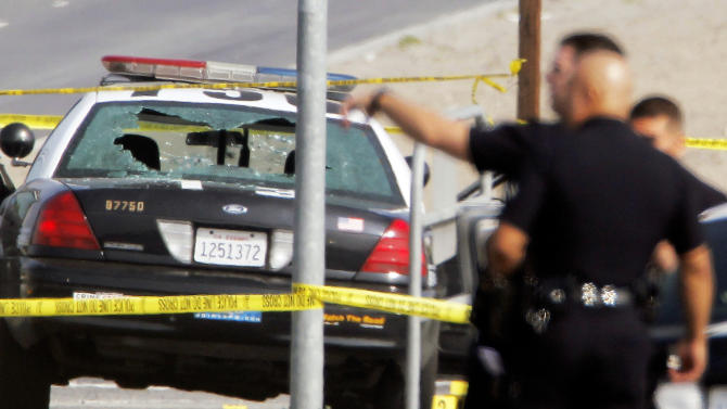 Police tape surrounds a bullet-damaged Los Angeles Police vehicle on Thursday Feb. 7, 2013 in Corona, Calif.  Former Los Angeles police officer Christopher Dorner is suspected if shooting at the two LAPD officers in the vehicle, who were sent to Corona to protect someone Dorner threatened in a rambling online manifesto. One officer's head was grazed by a bullet. Thousands of police officers throughout Southern California and Nevada hunted Thursday for Dorner, who was angry over his firing and began a deadly shooting rampage that he warned in an online posting would target those on the force who wronged him. (AP Photo/Nick Ut)