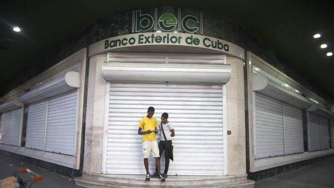 Teenagers play with a mobile phone in Havana