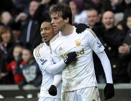 Swansea City's Michu celebrates with teammate Jonathan de Guzman after scoring a goal against Queens Park Rangers during their Premier League match at the Liberty Stadium in Swansea