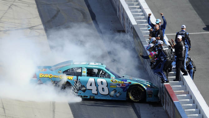 Jimmie Johnson (48) and his crew celebrate winning the NASCAR Sprint Cup Series FedEx 400 auto race at Dover International Speedway, Sunday, June 3, 2012, in Dover, Del. (AP Photo/Nick Wass)