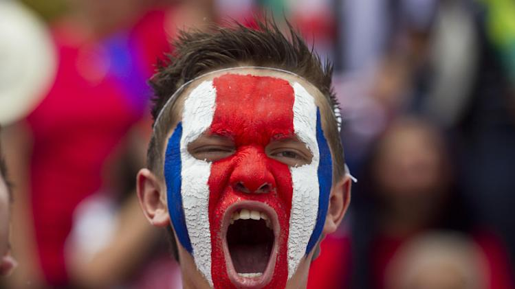 A Costa Rican soccer fans with his face painted in the country's national colors gets warmed up as he prepares to watch a round of 16 World Cup match against Greece, in San Jose, Costa Rica, Sunday, June 29, 2014