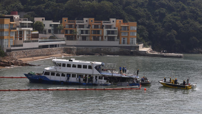 A group of firemen and police officers investigate on a salvaged boat which sank after colliding with a ferry near Lamma Island, off the southwestern coast of Hong Kong Island Wednesday, Oct. 3, 2012. An official with the ferry company involved in the collision that killed 38 people said Wednesday that the vessel recently passed inspection, but he had no details about how the crash occurred. (AP Photo/Kin Cheung)