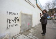 A woman takes a photograph of the former site of &quot;Banksy: Slave Labour&quot;, a mural attributed to graffiti artist Banksy, in north London February 20, 2013. The mural is up for sale at a Miami auction house after the work, and a chunk of the North London wall it was spray-painted on, vanished late last week. REUTERS/Neil Hall