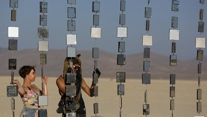 """Denise S. and Richard S. utilize an art installation during the Burning Man 2015 """"Carnival of Mirrors"""" arts and music festival in the Black Rock Desert of Nevada"""