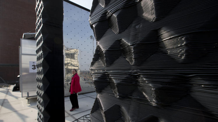 A visitor passes a 3D printer, rear, as she looks at part of a printed canal house, foreground, in Amsterdam, Netherlands, Thursday, March 13, 2014. Dutch architecture firm Dus has embarked on a project to build a 21st-century version of a classic Amsterdam canal house, printing it out piece by piece with an oversized 3-D printer, and then slotting them together like oversized Lego blocks. The goal is to discover and share the potential uses of 3-D printing in construction by creating new materials, trying out designs and testing building techniques. (AP Photo/Peter Dejong)