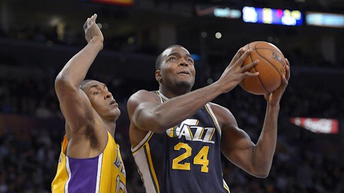 Utah Jazz forward Paul Millsap, right, goes up for a shot as  Los Angeles Lakers forward Metta World Peace defends during the first half of an NBA basketball game, Friday, Jan. 25, 2013, in Los Angeles. (AP Photo/Mark J. Terrill)
