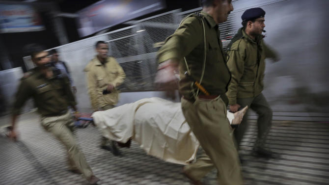Indian police carry the body of a pilgrim who was killed in a stampede on a railway platform at the main railway station in Allahabad, India, Sunday, Feb. 10, 2013. At least ten Hindu pilgrims attending the Kumbh Mela were killed and more then thirty were injured in a stampede on an overcrowded staircase, according to Railway Ministry sources. (AP Photo/Kevin Frayer)