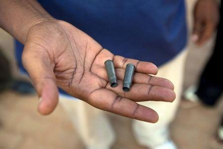 A man holds bullet cases he said were shot by the presidential guard in Ouagadougou