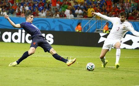 van Persie of the Netherlands shoots past Spain's Pique to score his team's fourth goal during their 2014 World Cup Group B soccer match at the Fonte Nova arena in Salvador