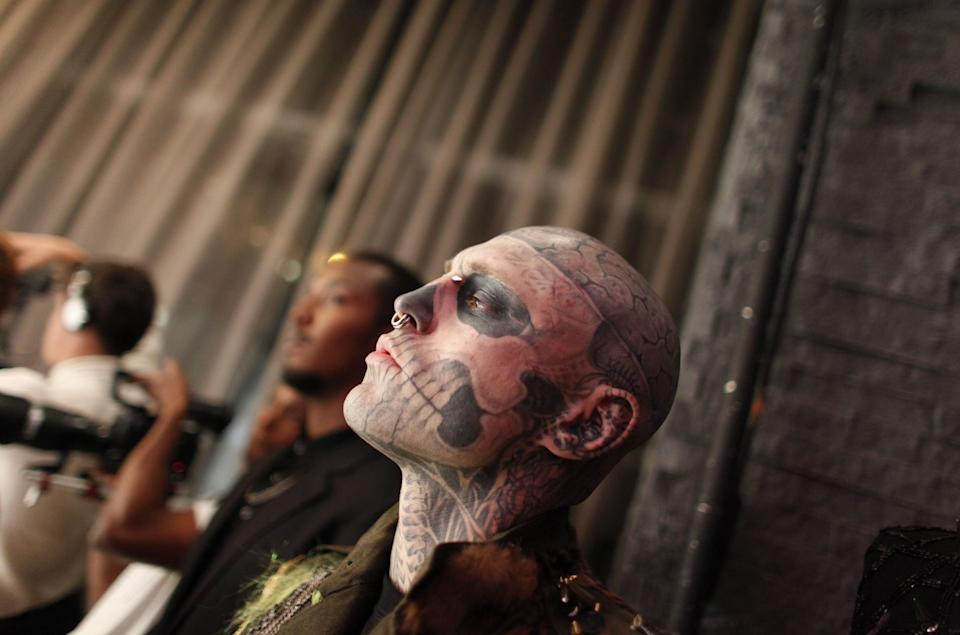 A guest with tattoos on his face arrives for the Betsey Johnson Spring 2013 collection show during Fashion Week, Tuesday, Sept. 11, 2012, in New York. (AP Photo/Jason DeCrow)