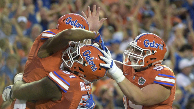 Florida wide receiver Demarcus Robinson, left, is congratulated by offensive lineman Antonio Riles (51) and offensive lineman Cameron Dillard (54) after catching a 36-yard pass in the end zone for a touchdown during the first half of an NCAA college football game against Mississippi Saturday, Oct. 3, 2015, in Gainesville, Fla. (AP Photo/Phelan M. Ebenhack)