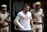 Delhi policemen escort Australian cricketer Luke Pomersbach to a court appearance in New Delhi on May 18. Pomersbach was granted bail by a New Delhi court following accusations he molested a woman and beat up her fiance, his lawyer told AFP