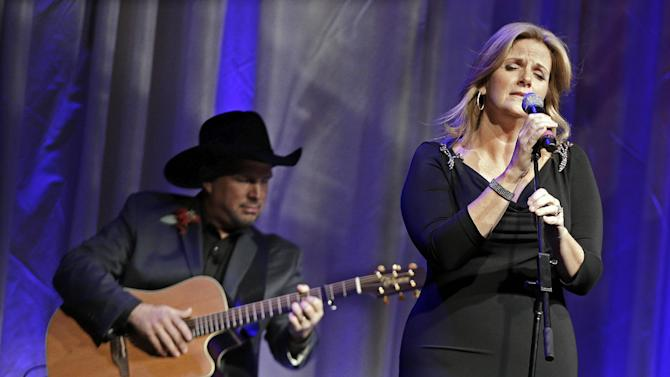 "Trisha Yearwood is accompanied by her husband, Garth Brooks, as she sings ""Wind Beneath My Wings,"" a song written by Larry Henley, as Henley is inducted into the Nashville Songwriters Hall of Fame on Sunday, Oct. 7, 2012, in Nashville, Tenn. (AP Photo/Mark Humphrey)"