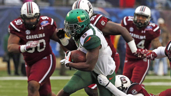 Miami running back Duke Johnson (8) breaks away from a tackle attempt by South Carolina safety Kadetrix Marcus in the first half of the Independence Bowl NCAA college football game in Shreveport, La., Saturday, Dec. 27, 2014.(AP Photo/Rogelio V. Solis)